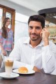 Usmívající se muž pomocí mobilního telefonu v kavárně