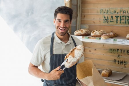 Confident cafe owner with sweet food at coffee shop