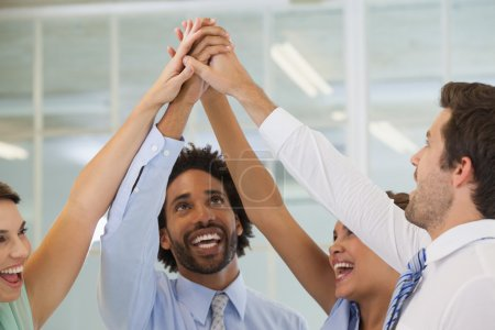 Portrait of a cheerful business team joining hands...