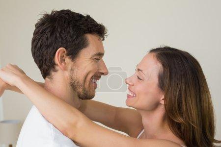 Photo pour Vue latérale d'un jeune couple d'amoureux regardent à la maison - image libre de droit