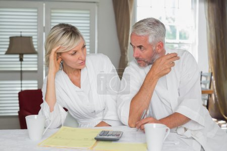Photo for Serious mature couple sitting with home bills and calculator at table - Royalty Free Image
