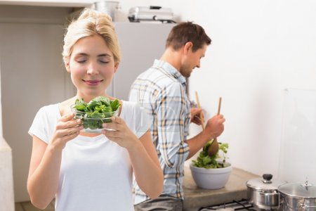 Photo for Smiling young woman holding bowl of leaves with man preparing salad in the background in kitchen at home - Royalty Free Image