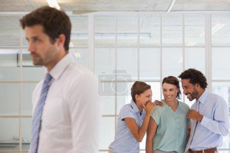 collègues commérages avec triste homme d'affaires au premier plan