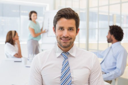 Photo for Portrait of a smiling businessman with colleagues in meeting in background at the office - Royalty Free Image