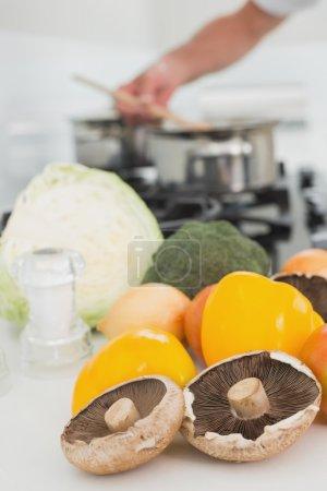 Detail of vegetables with man preparing food in background