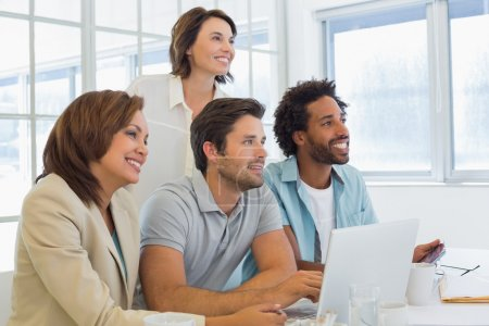 Photo for Smiling young business people using laptop in meeting at office desk - Royalty Free Image