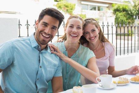 Photo pour Portrait de trois amis heureux buvant café au café - image libre de droit