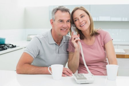 Happy couple using landline phone together in kitchen
