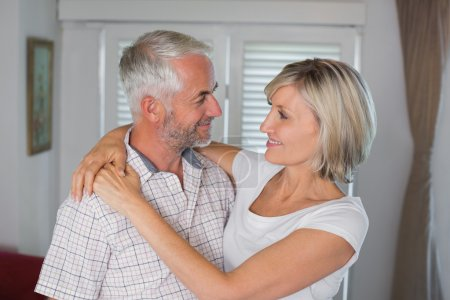 Photo for Smiling woman embracing mature man at home - Royalty Free Image
