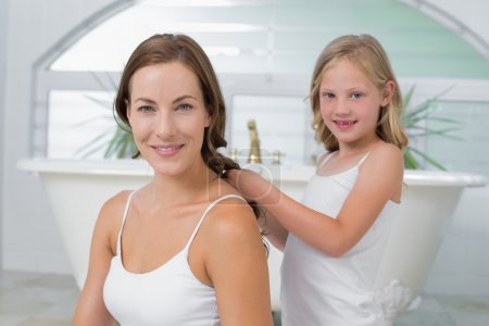 Cute little girl braiding mother's hair in bathroom