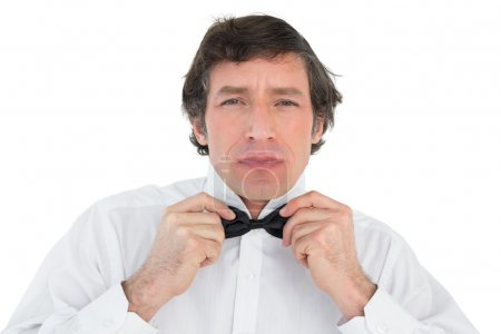 Photo for Portrait of handsome groom corrects bow tie over white background - Royalty Free Image