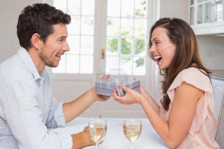 Man giving happy woman a gift box at home