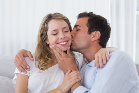 Close-up of a man kissing happy woman
