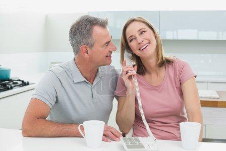 Happy couple using landline phone in kitchen