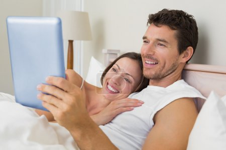 Couple using digital tablet in bed