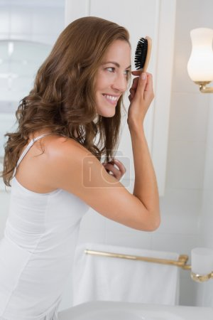 Side view of a beautiful young woman brushing her hair