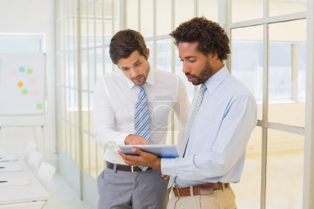 Photo for Two young businessmen looking at digital tablet in the office - Royalty Free Image