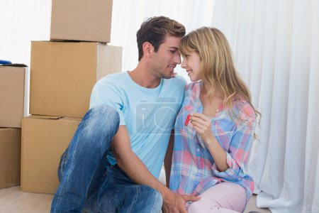 Photo for Happy loving young couple holding new house key against cardboard boxes - Royalty Free Image