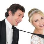 Portrait of attractive bride pulling tie of groom ...