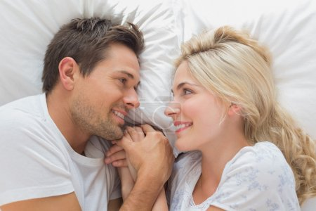 Photo pour Détendu épris de jeune couple à la recherche à l'autre en position couchée dans son lit à la maison - image libre de droit