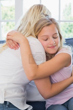 Girl with eyes closed embracing mother