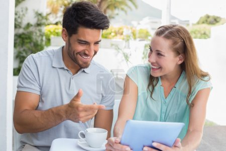 Happy couple with coffee cup using digital tablet at cafe