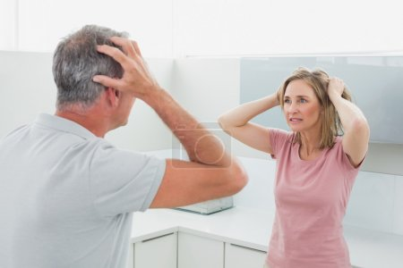 Photo for Unhappy couple having an argument in the kitchen at home - Royalty Free Image