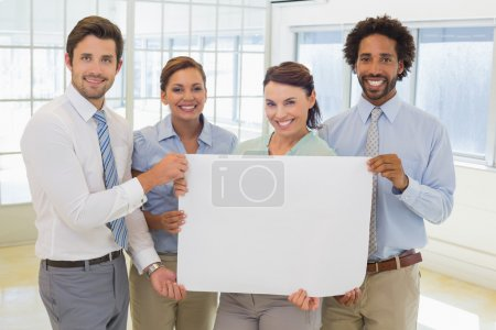 Photo for Group portrait of happy business colleagues holding blank placard in the office - Royalty Free Image