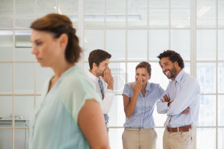 collègues commérages avec triste femme d'affaires au premier plan