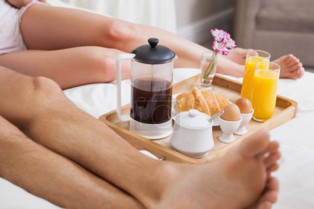 Low section of couple having breakfast in bed
