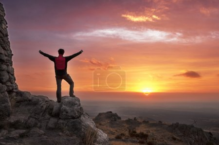 Man on top of a mountain victorious admiring the sunrise