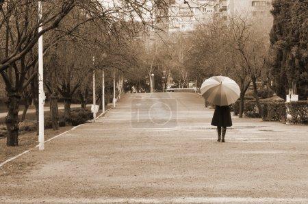 Photo pour Femme qui marche avec parapluie dans le parc un jour de pluie - sépia - image libre de droit