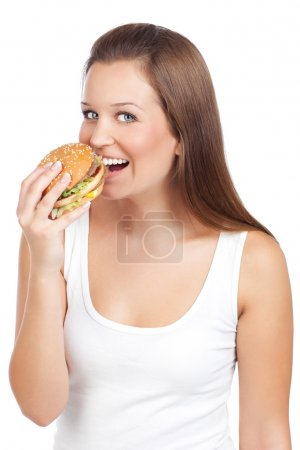 Photo for Young woman eating hamburger, isolated on white - Royalty Free Image