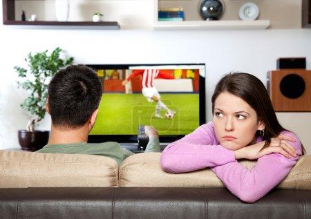 Photo pour Image de femme s'ennuyée, tandis que son partenaire regarder sport - image libre de droit