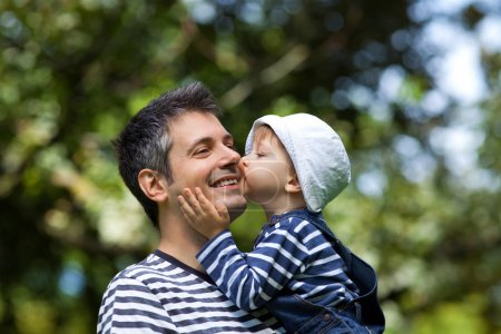 Photo for Image of a child kissing a father on a cheek, shallow depth of field - Royalty Free Image