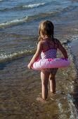 Holčička s růžovým float vypadá opatrně na vodu