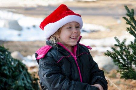 Happy little girl wearing a Santa hat