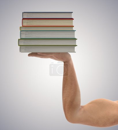 Stack of books in the hands a strong man