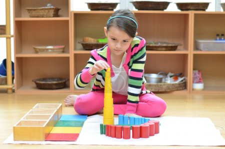 Photo for Little girl hand building tower made of montessori educational materials - Royalty Free Image