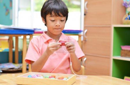Photo pour Petit garçon avec des perles de couleur matérielle Montessori - image libre de droit