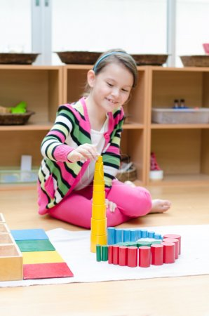 Photo for Little girl hand building tower made of montessori educational material - Royalty Free Image