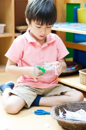 Photo for Little boy cutting paper of montessori educational - Royalty Free Image