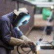 Worker with protective mask welding metal...