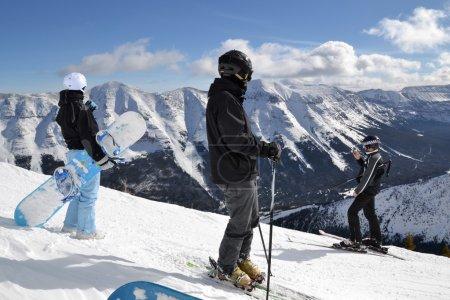 Photo pour Groupe de skieurs et snowboarders regardant le paysage montagneux - image libre de droit