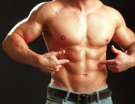 Photo for Muscular young man showing abs. - Royalty Free Image
