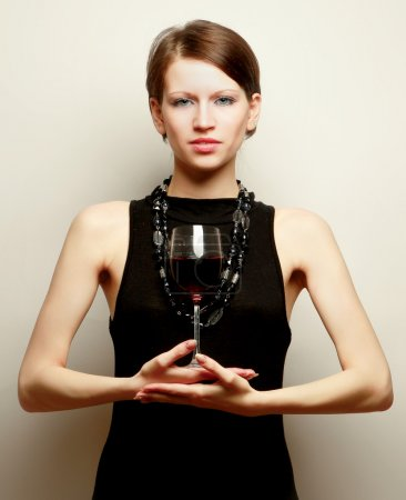 Photo for Portrait of a beautiful woman with a wineglass over the wall, isolated on grey - Royalty Free Image