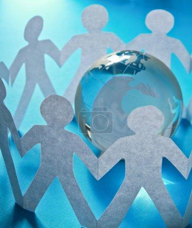 Photo pour Papier gens debout dans un cercle autour du globe de verre isolé sur fond bleu - image libre de droit