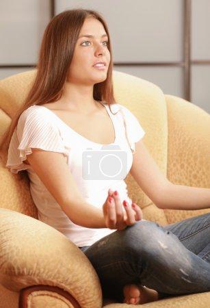 Photo pour Jeune femme assise sur un canapé en position lotus méditant - image libre de droit