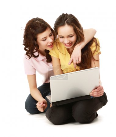 Two girls twins with laptop isolated on the white