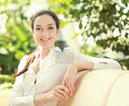 Photo pour Une jeune femme souriante assise sur le canapé à la maison - image libre de droit